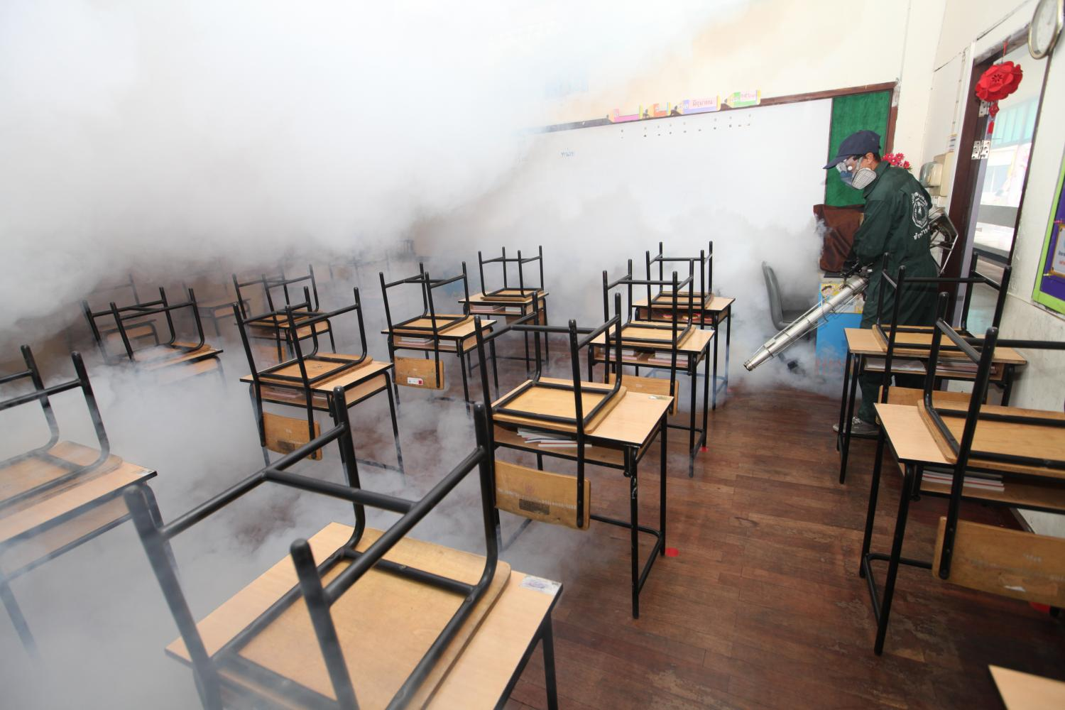 A Bang Rak district official on Monday sprays mosquito repellent in a classroom at Wat Hua Lamphong School to prepare for the new term that will begin on July 1. (Photo by Arnun Chonmahatrakool)