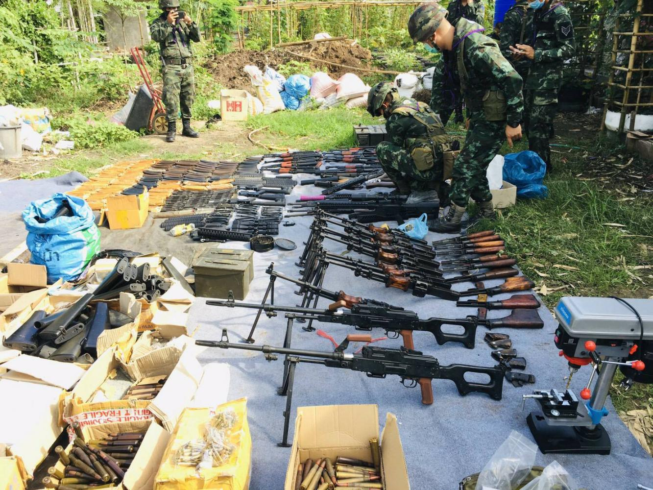 Soldiers display weapons and ammunition found at a home in Tak's Mae Sot district on Tuesday. The weapons are suspected to be part of a plot to stir up political unrest. POLICE PHOTO