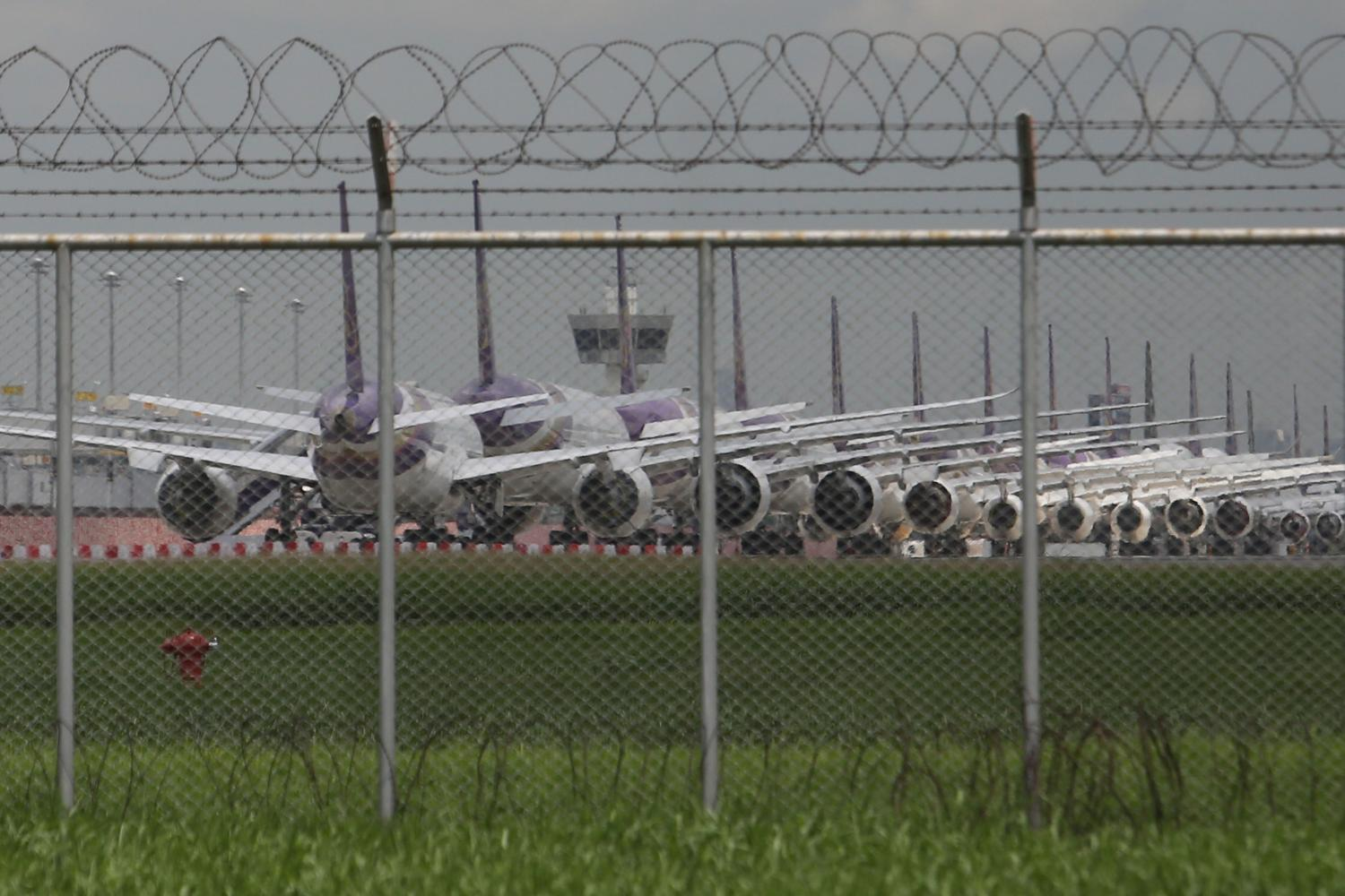 Thai Airways airplanes are seen parked on the tarmac at Suvarnabhumi airport. The Civil Aviation Authority of Thailand has laid out further measures to help airlines cope with the Covid-19 pandemic. Wichan Charoenkiatpakul