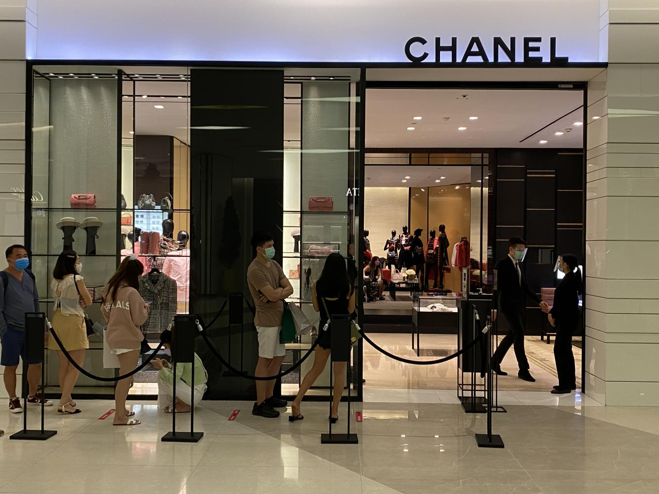 Customers wear face masks while waiting in a queue outside the Chanel store at Siam Paragon. Tourists from CLMV nations account for many of the foreign visitors at the mall.Bangkok Post