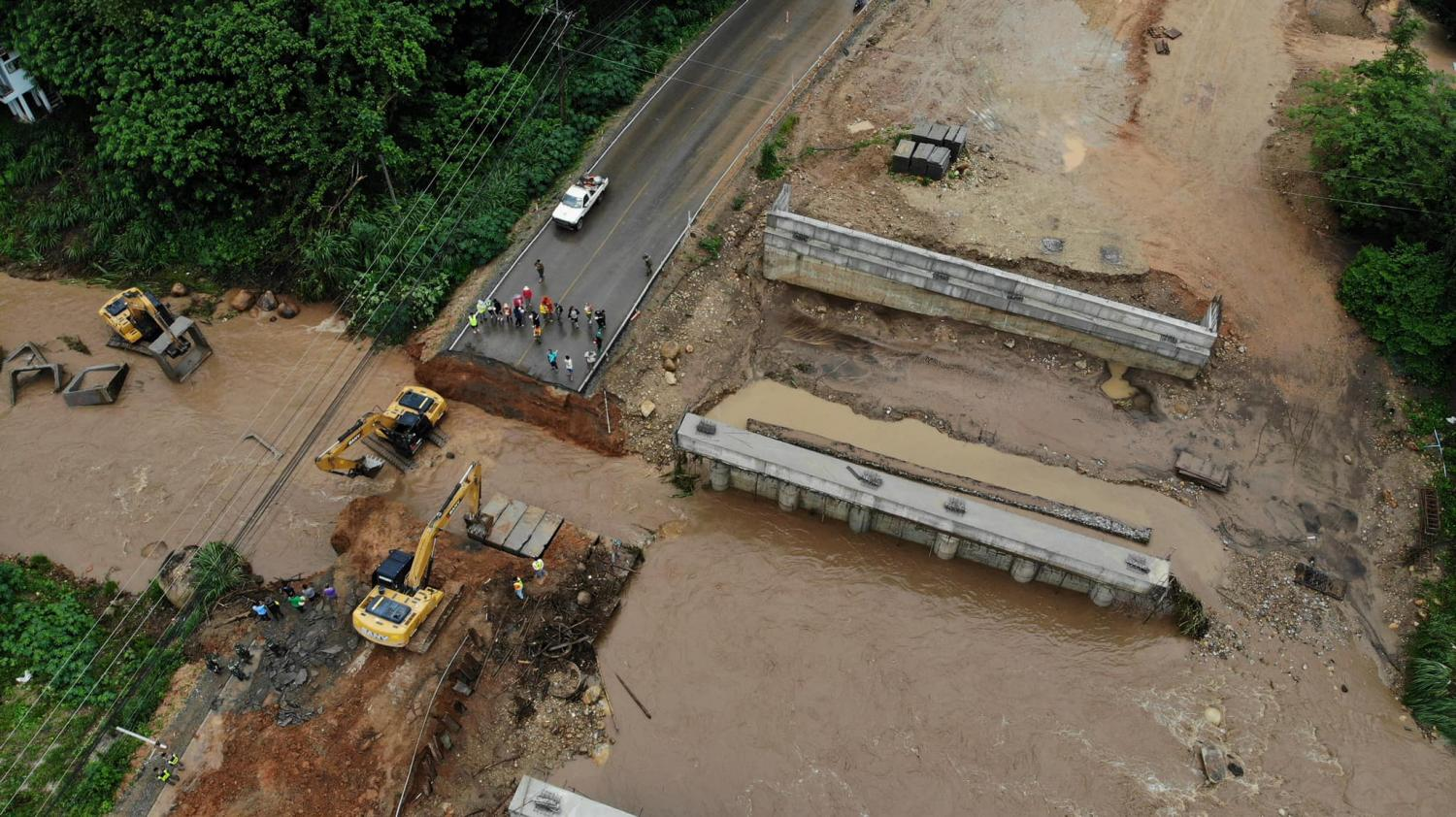 Hasty service: Workers repair the Chiang Mai-Chiang Rai road, which had flooded after torrential water runoff in Doi Saket district of Chiang Mai on Friday night. The repair was expected to be wrapped up by yesterday evening.