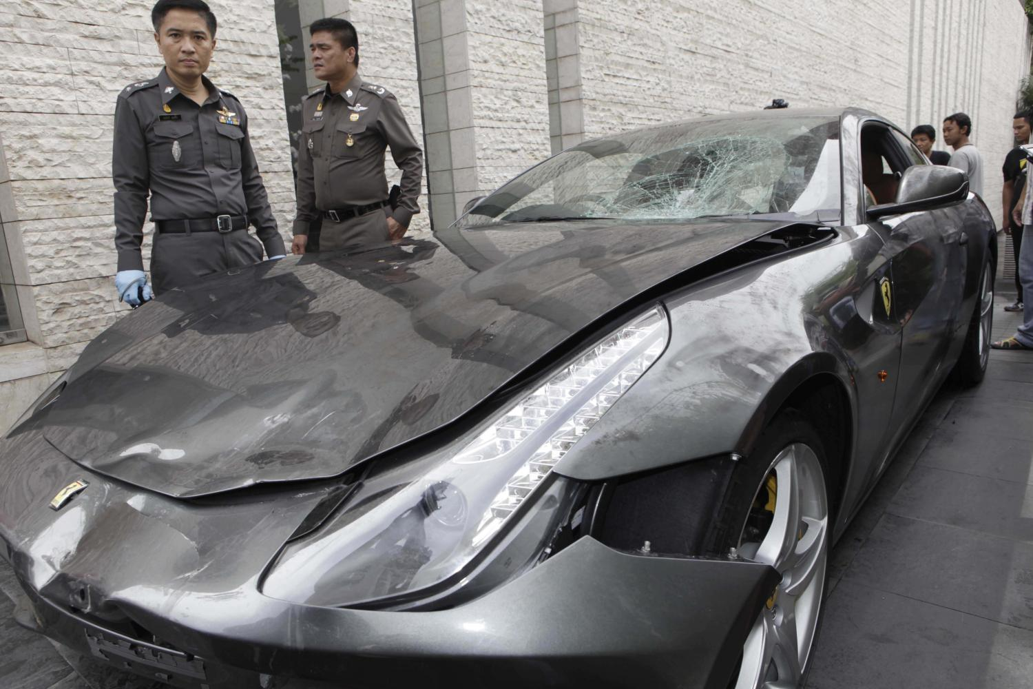 In this 2012 file photo, police officers inspect the luxury car involved in the notorious hit-and-run case involving Vorayuth 'Boss' Yoovidhya. Mr Vorayuth who fled the country afterwards remains a free man as authorities allowed charges against him to expire one by one.Bangkok Post photo