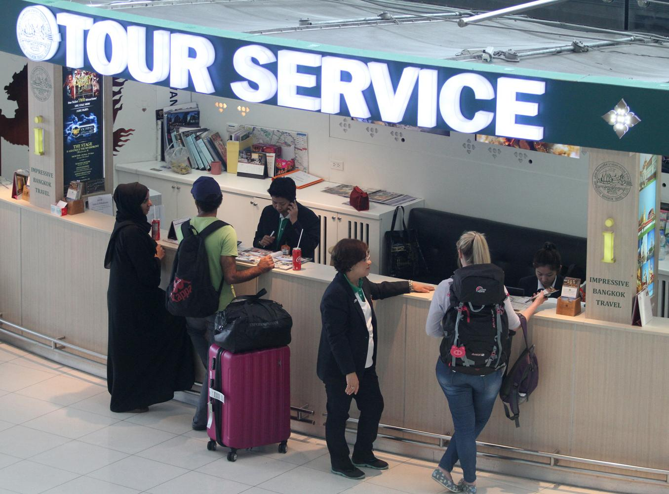 Foreigners check out tour service offerings at a Suvarnabhumi airport counter.  (Photo by Thanarak Khunton)