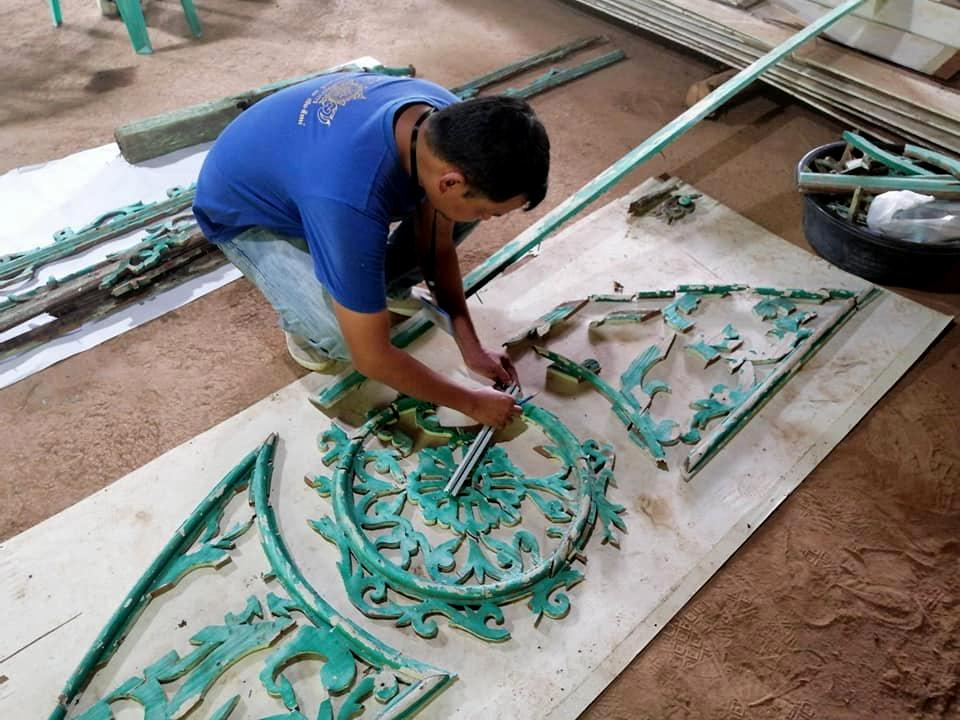 A fine arts official is assembling debris that used to decorate the gable of ancient Bombay Burmah house that was torn down in a restoration project. (Picture courtesy of Fine Arts Department)