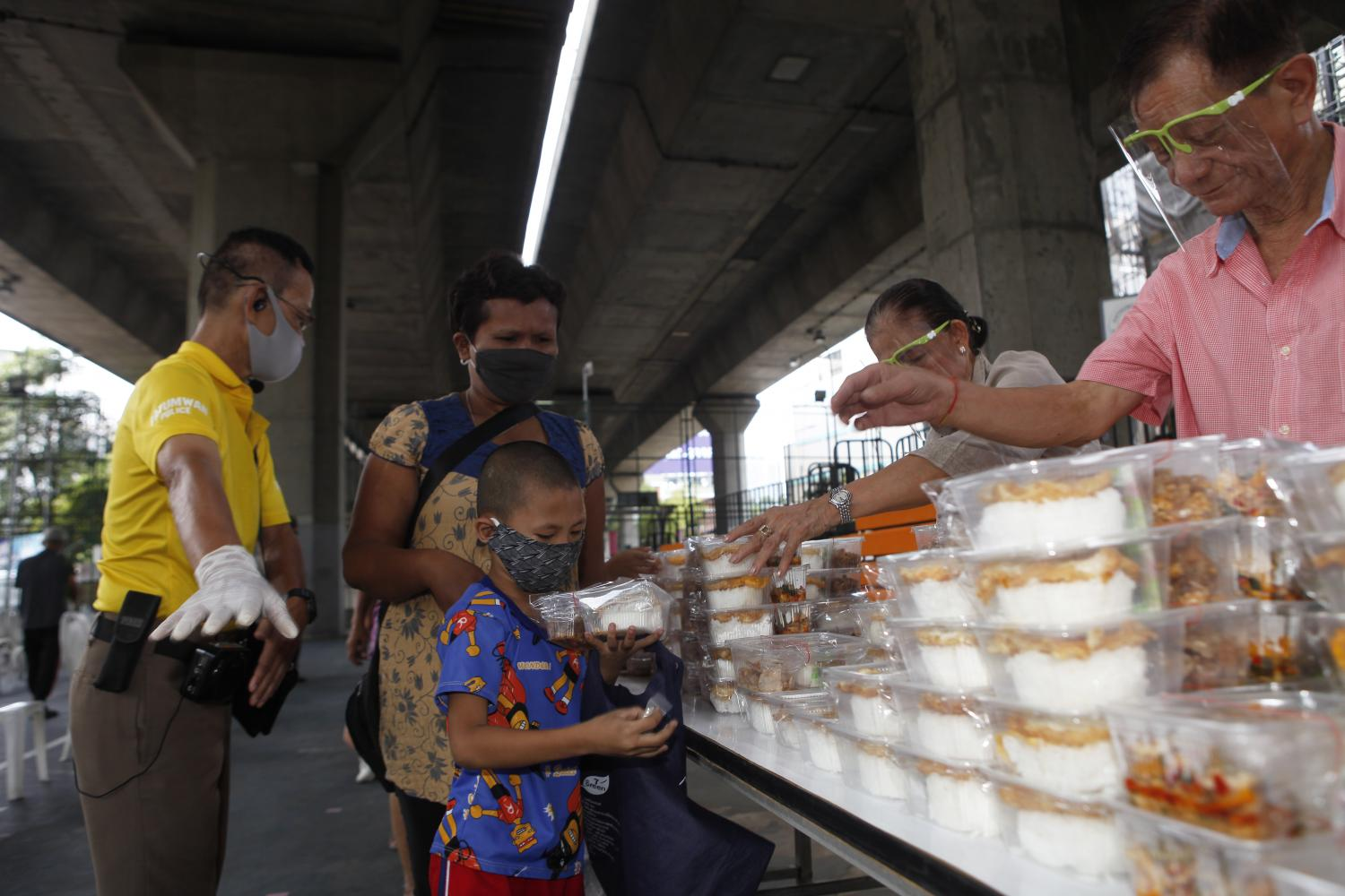 A young boy receives donated food at a sports ground in Pathumwan district of the capital. Covid-19 has unleashed an unprecedented economic shock in Thailand. (Photo by Nutthawat Wicheanbut)