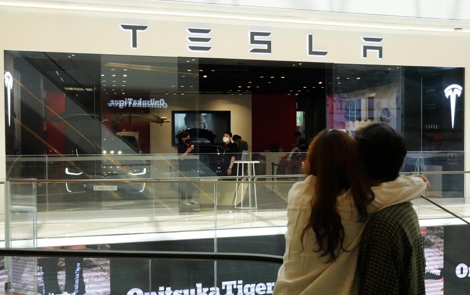 A couple looks at a Tesla dealership in Hanam.(Reuters photo)