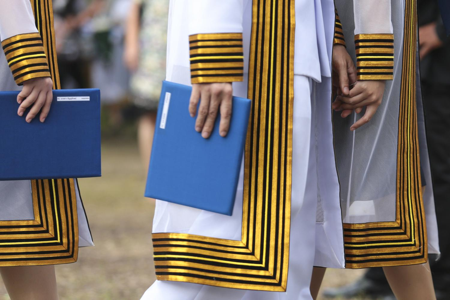 New Chulalongkorn graduates hold their degrees after a graduation ceremony.