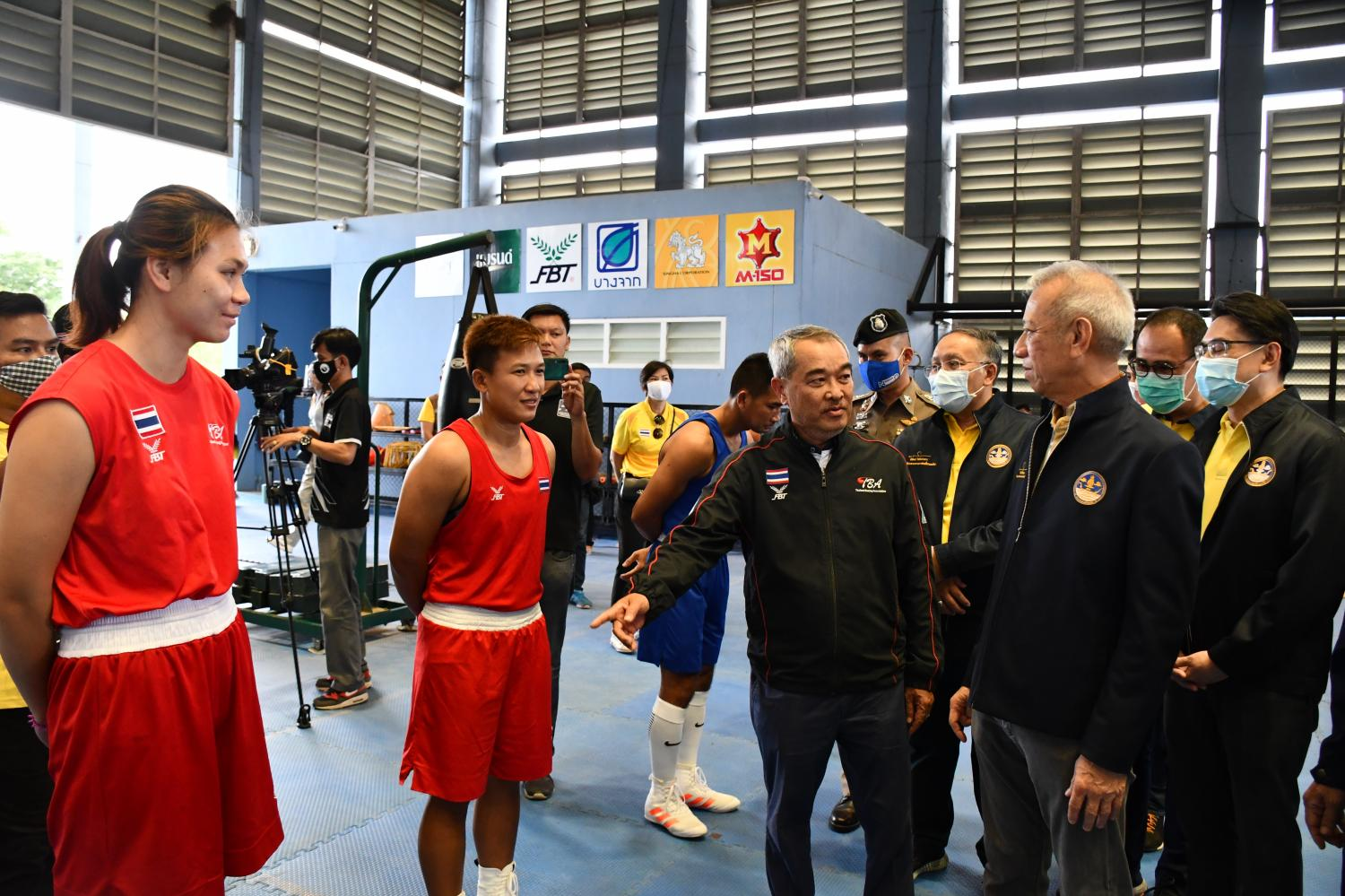 Minister of Tourism and Sports Phiphat Ratchakitprakarn (right) speaks to the members of the Thai national boxing team.