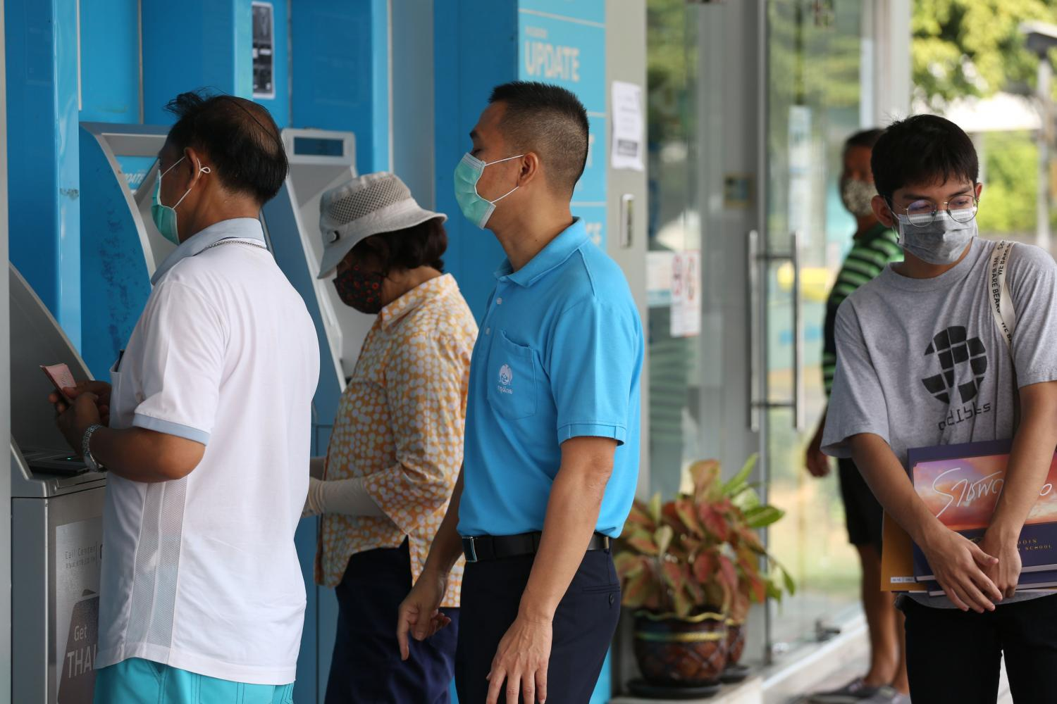 Customers queue at a Krungthai Bank ATM on Nawamin Road to receive a cash handout offered by the government. The Social Security Office expects to start issuing 5,000-baht monthly handouts within 10 days.