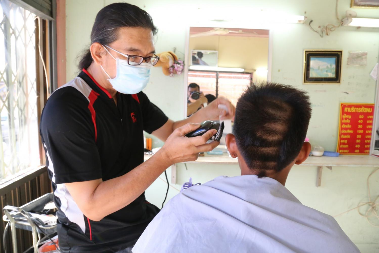 In this file photo, a barber in Chai Nat tries to fix a male student's shorn hair, a typical punishment by school teachers, which is against the students' human rights.Bangkok Post
