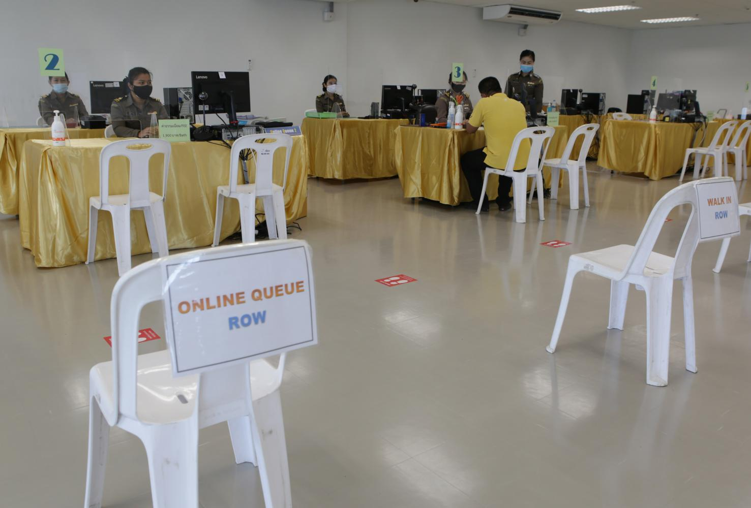 Social-distancing measures are put in place at a temporary centre for immigration services in Nonthaburi's Pak Kret district that is now open to foreign visitors seeking short-stay extensions. (Photo by Apichit Jinakul)