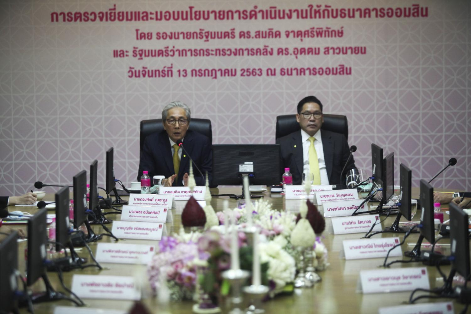 Deputy Prime Minister Somkid Jatusripitak is accompanied by Finance Minister Uttama Savayana (right) during the meeting held at the headquarters of the Government Savings Bank. (Photo by Arnun Chonmahatrakool)