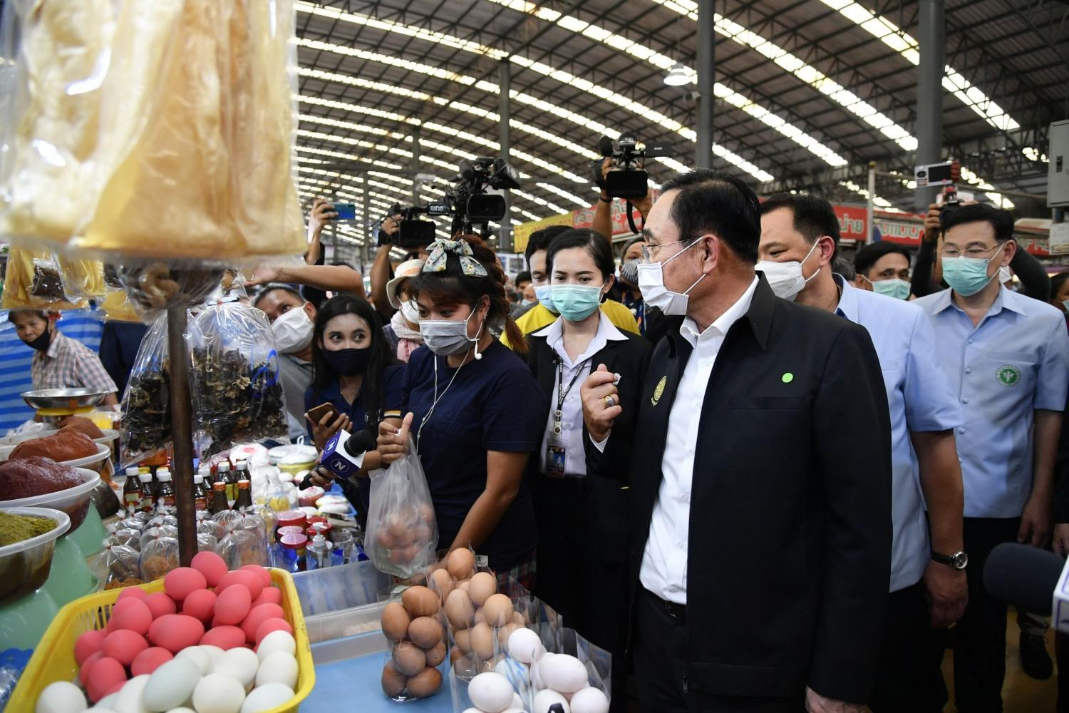 Prime Minister Prayut Chan-o-cha, accompanied by Public Health Minister Anutin Charnvirakul and his deputy Sathit Pitutecha, chats with vendors at the Star Market in downtown Rayong.(Government House photo)