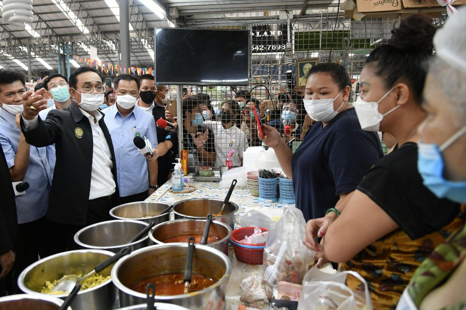 Prime Minister Prayut Chan-o-cha gestures as he talks with vendors in a market in Rayong as the province is gripped by fear over a second Covid-19 wave following a recent visit by an infected Egyptian airman. (Picture courtesy of Government House)