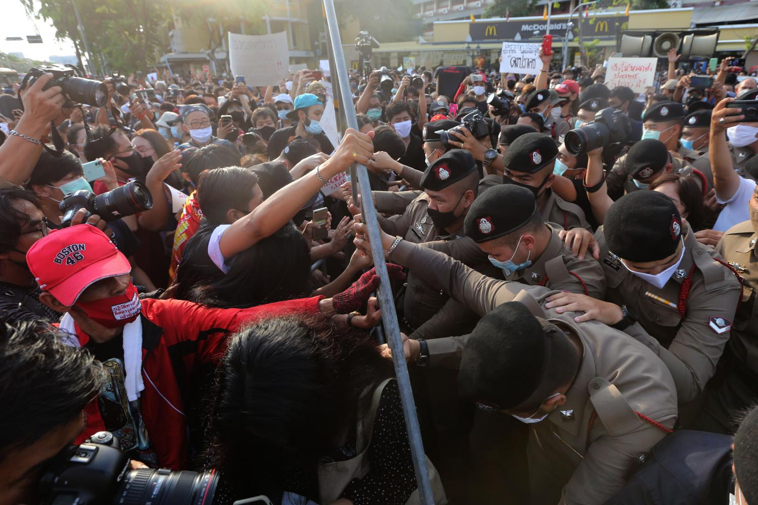 Battle of wills: Protesters from the Student Union of Thailand and the Free Youth group attempt to break past security barricades around the Democracy Monument as police officers try to stop them from demonstrating.