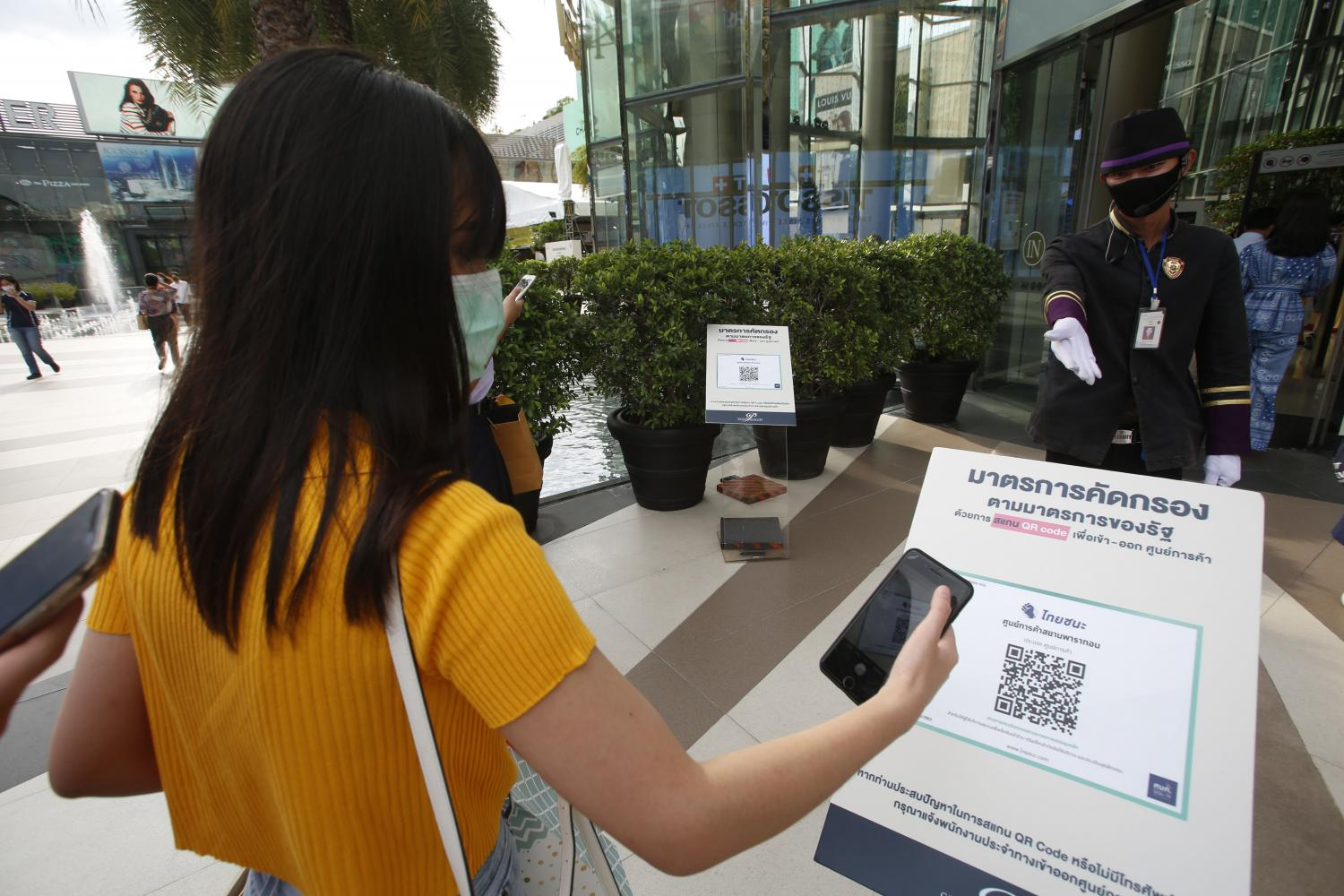 A shopper scans the Thai Chana QR code while checking in at Siam Paragon mall. The app was developed by state-owned Krungthai Bank. Pornprom Satrabhaya
