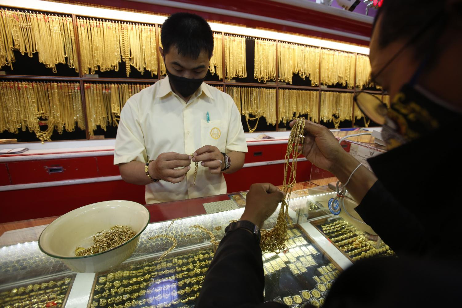 A trader inspects ornaments at a gold shop on Yaowarat Road. The local gold price is up moderately as the baht strengthens. (Photo by Pornprom Satrabhaya)