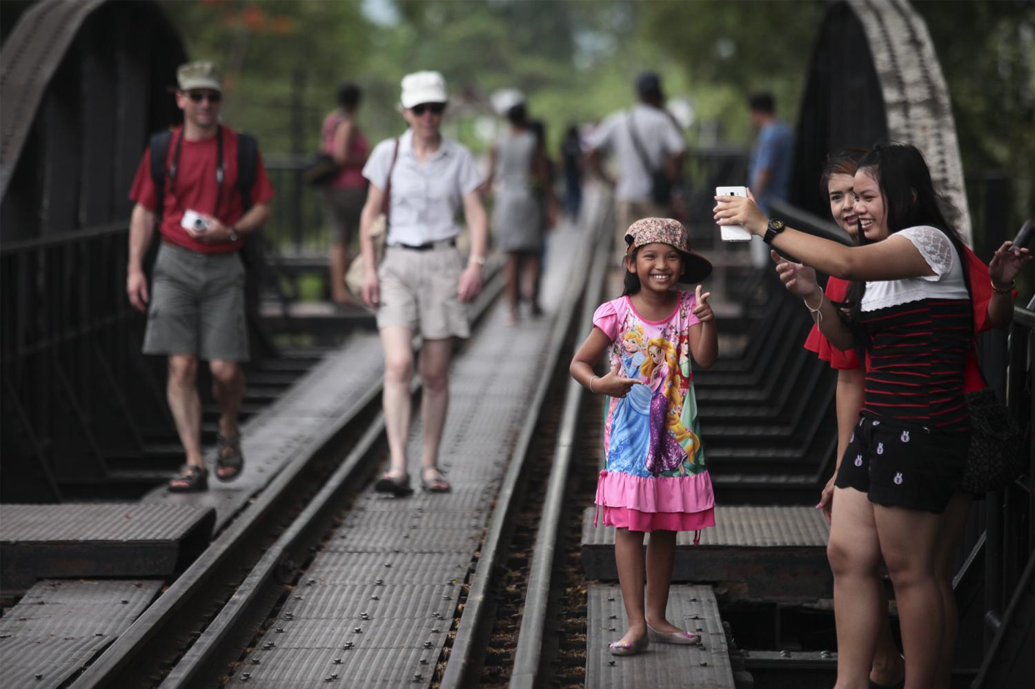 Tourists pose for pictures on the bridge on the River Kwai, a popular tourist site in Kanchanaburi province.