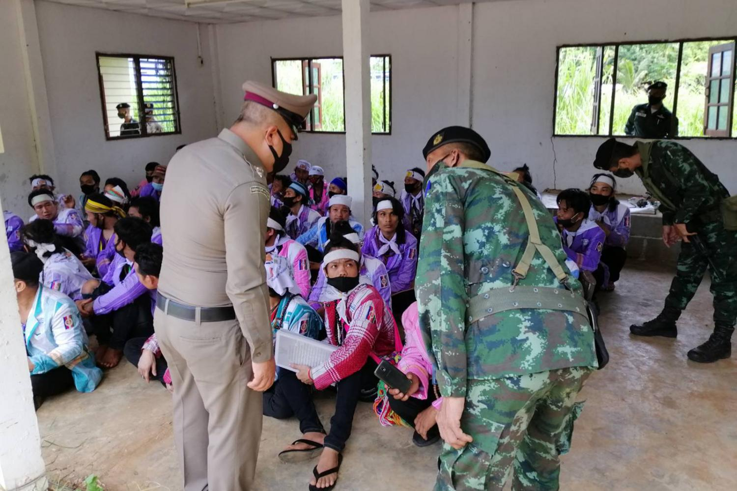 Police and military officers question some of the 78 ethnic-Karen people who were caught after crossing from a neighbouring country and charged with illegal entry in Thong Pha Phum district of Kanchanaburi on July 19.