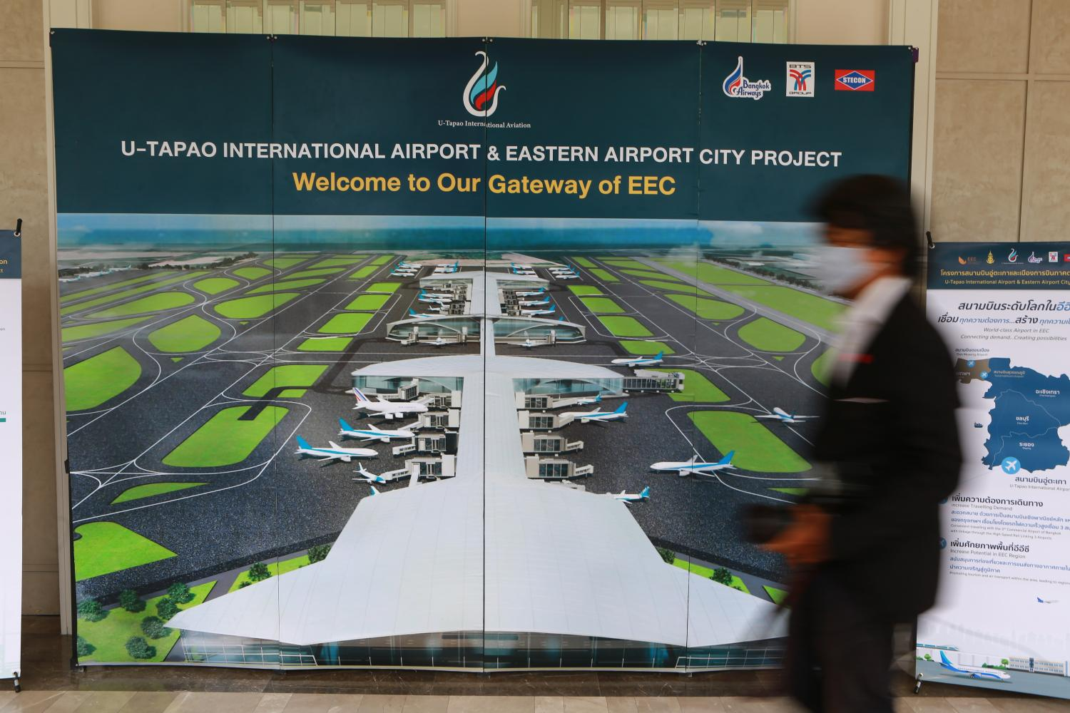 A man walks past a signboard promoting projects at U-tapao airport.(Photo by Somchai Poomlard)
