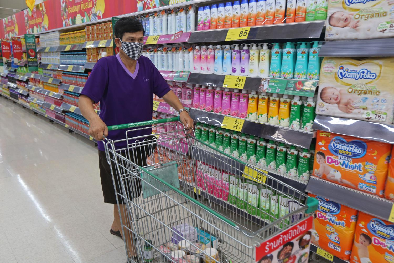 A shopper wearing a face mask browses consumer products at a Tesco Lotus. Varuth Hirunyatheb