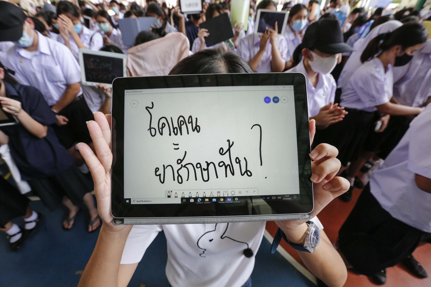 A protesting Triam Udom Suksa School student displays a message reading 'cocaine = dental medicine?' to ridicule the high-profile hit-and-run case involving Red Bull scion Vorayuth Yoovidhya during the anti-government rally at their campus on Friday. (Photo by Pattarapong Chatpattarasill)