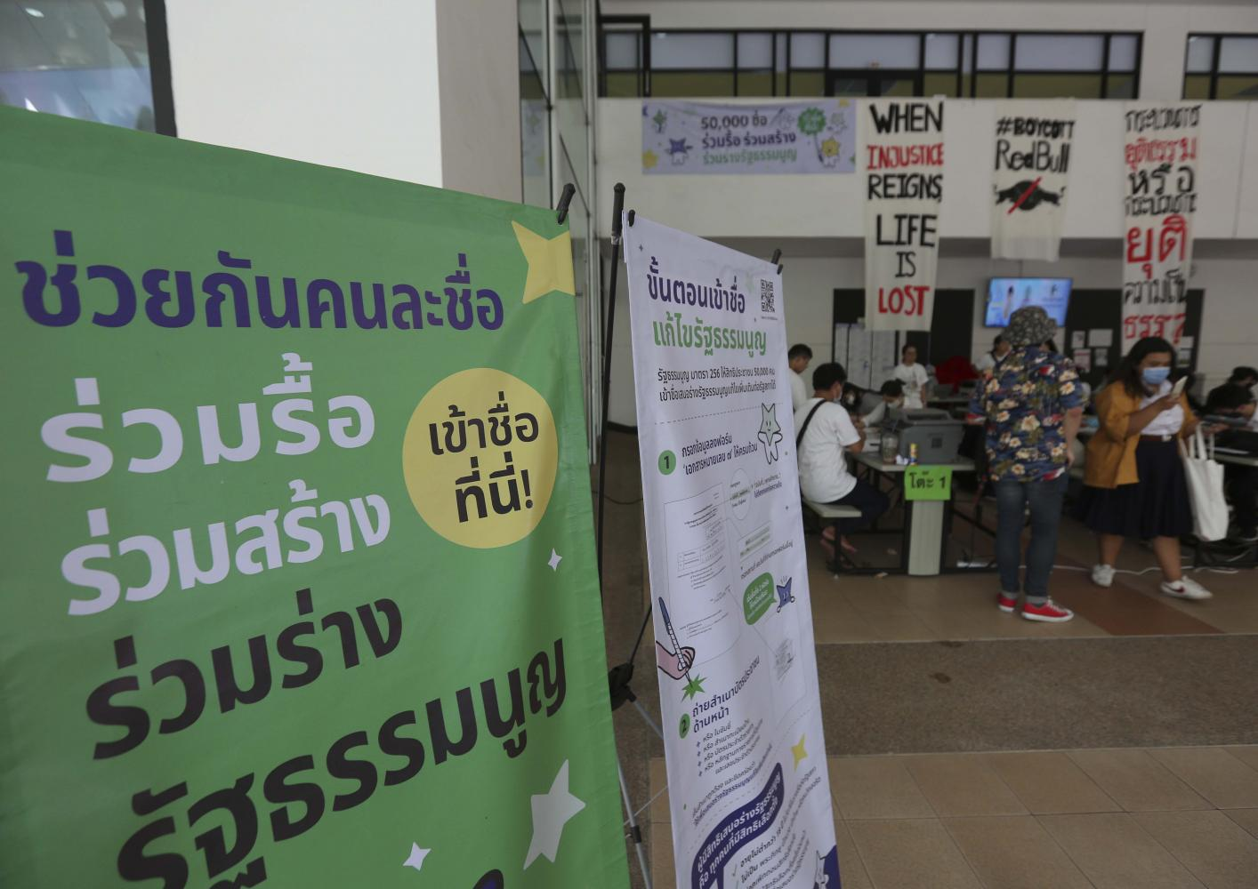 Pro-democracy students put up a sign encouraging people to sign up for a charter amendment campaign. (Photo by Pattarapong Chatpattarasill)