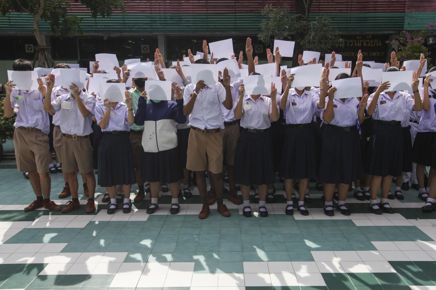 Students from several schools in and outside of Bangkok give the three-fingered salute in a symbolic protest against the government. Some also tied white ribbons to their bags to show their opposition. The Education Ministry has allowed the students to express their political views on school premises. (Photos by Samut Kongwarakom, Arnun Chonmahatrakool and the internal security operations command)