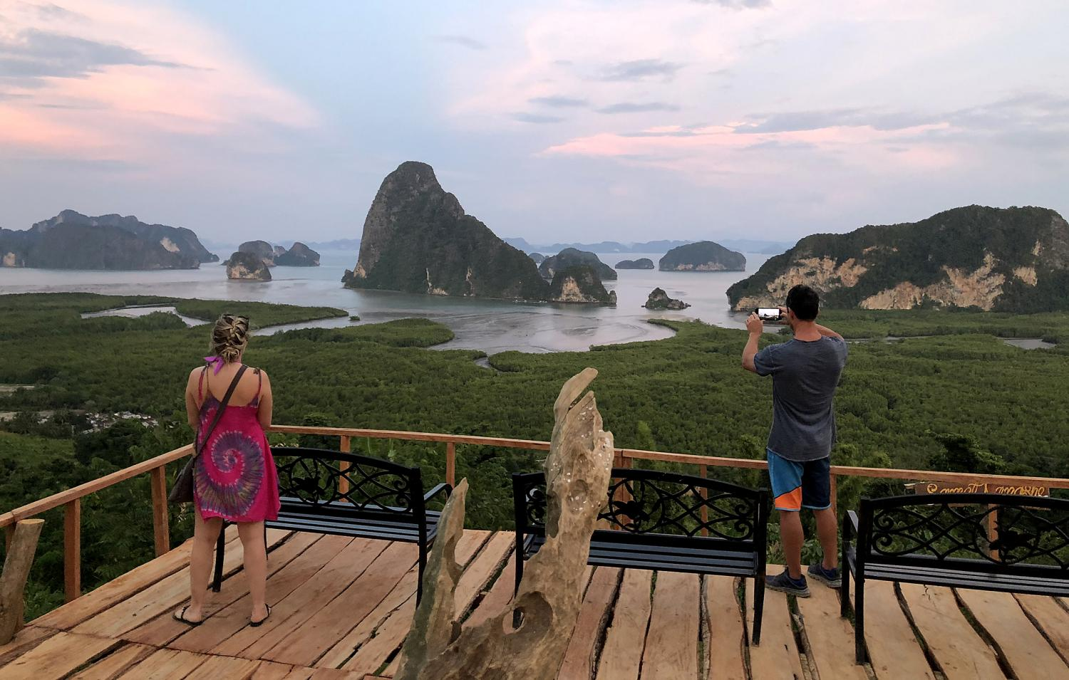 Foreign tourists take photos at the Samed Nang Chee viewpoint in Phangnga province. The Thai Hotels Association has asked the government to extend tourism stimulus benefits to expatriates in Thailand. (Photo by Sarot Meksophawan­nakul)