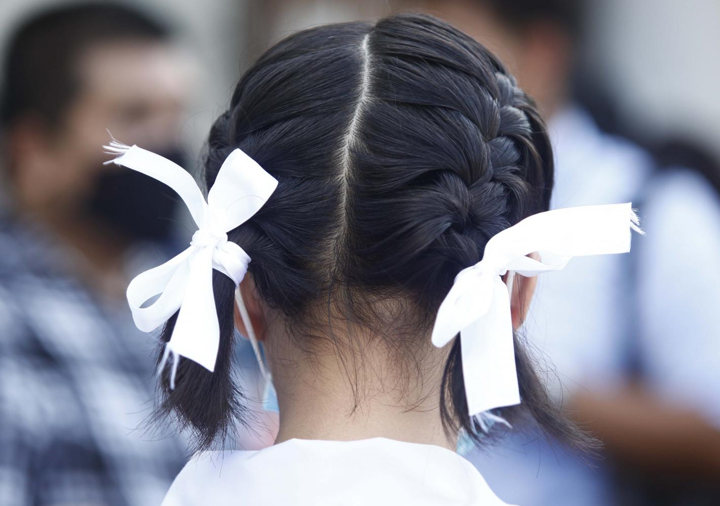 White ribbons are worn by students as a symbol that they stand in unity amid anti-government protests.