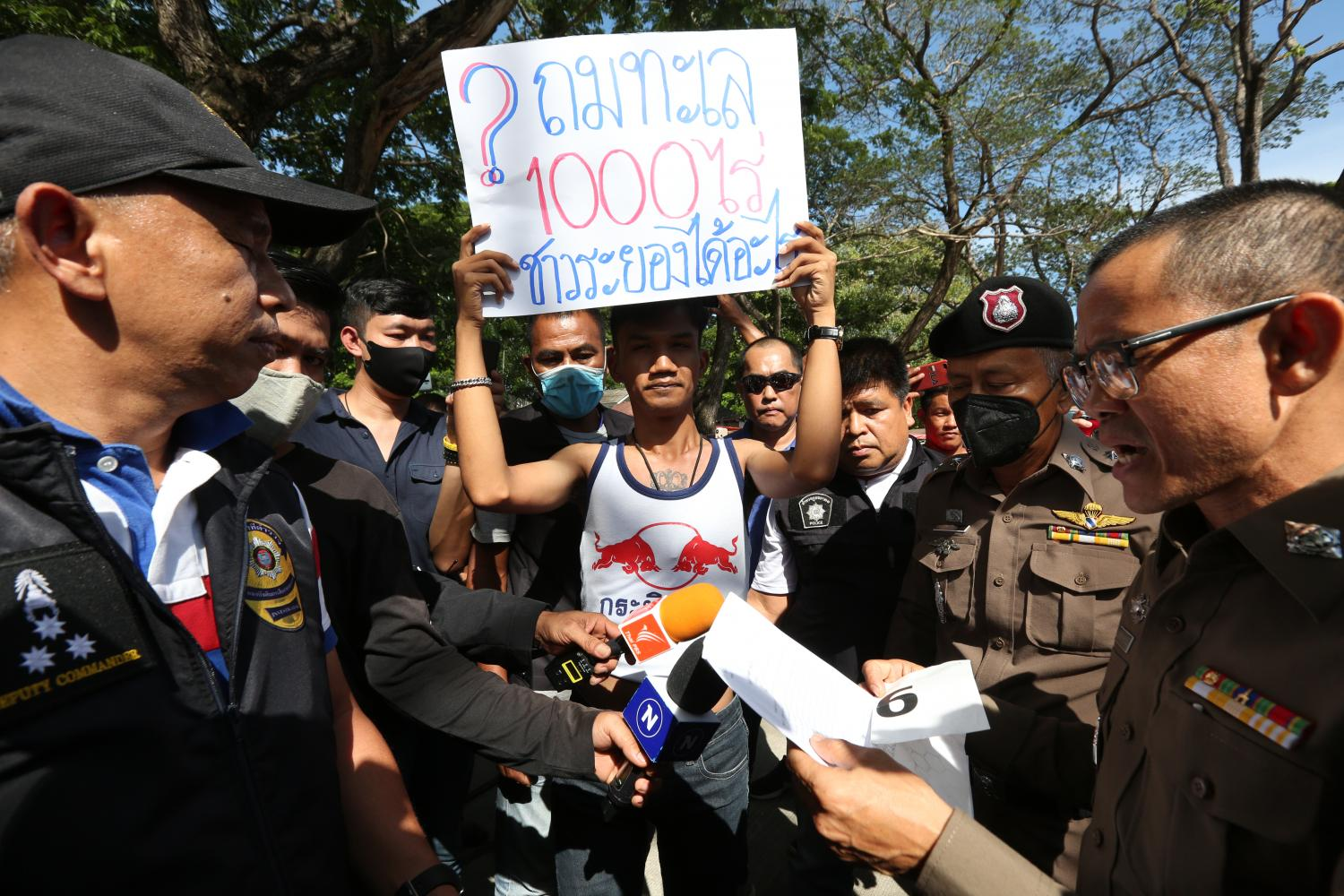 Activist Panupong Jadnok yesterday holds up a poster saying '1,000-rai sea reclamation. What will Rayong people get?' during Prime Minister Chan-o-cha's visit to a market ahead of Tuesday's mobile cabinet meeting.(Photo by Pattarapong chatpattarasill)