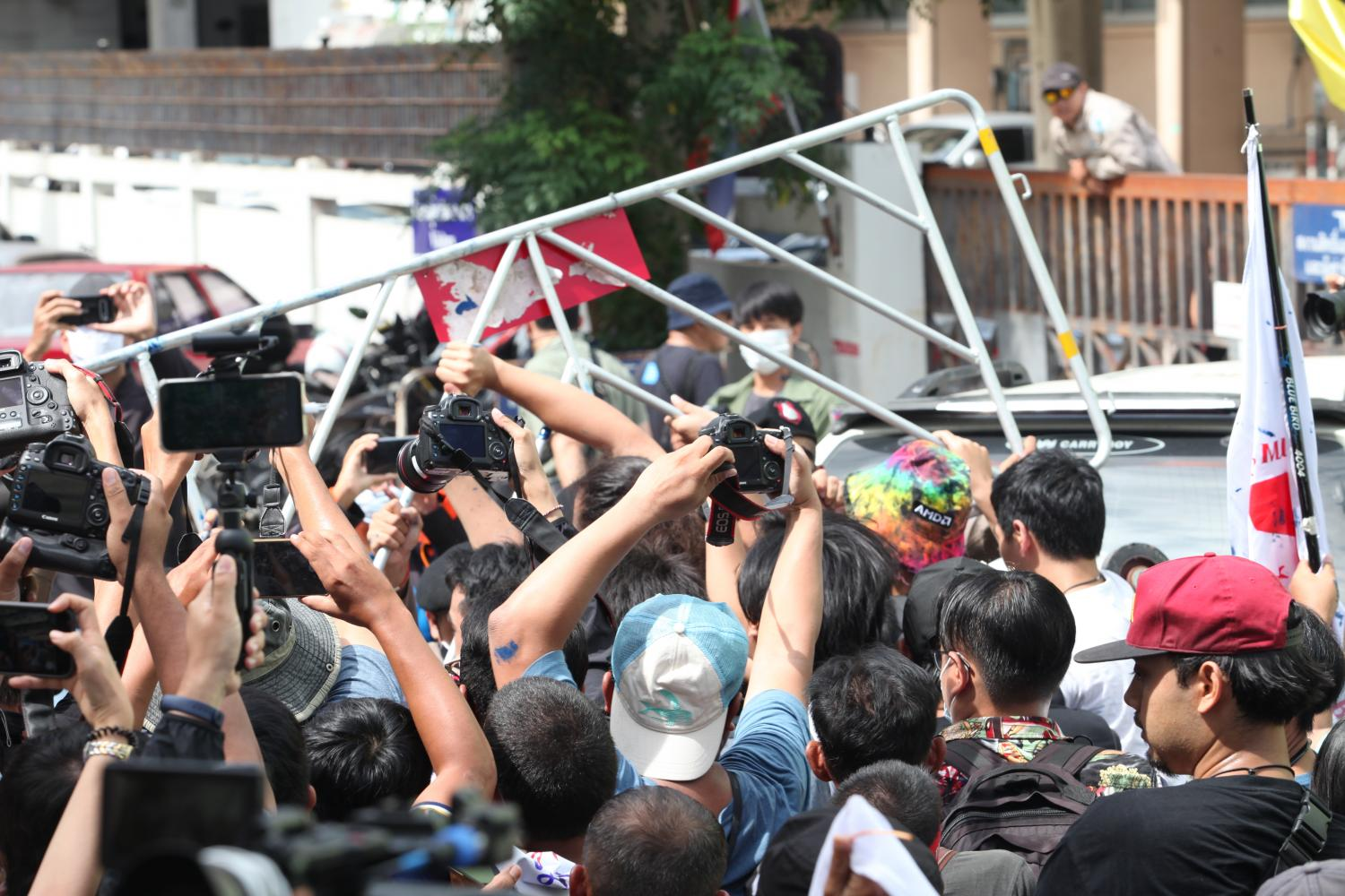 Supporters of pro-democracy activists break a police barricade around Samran Rat police station where the activists acknowledged charges relating the July 18 rally.(Photo by Apichart Jinakul)