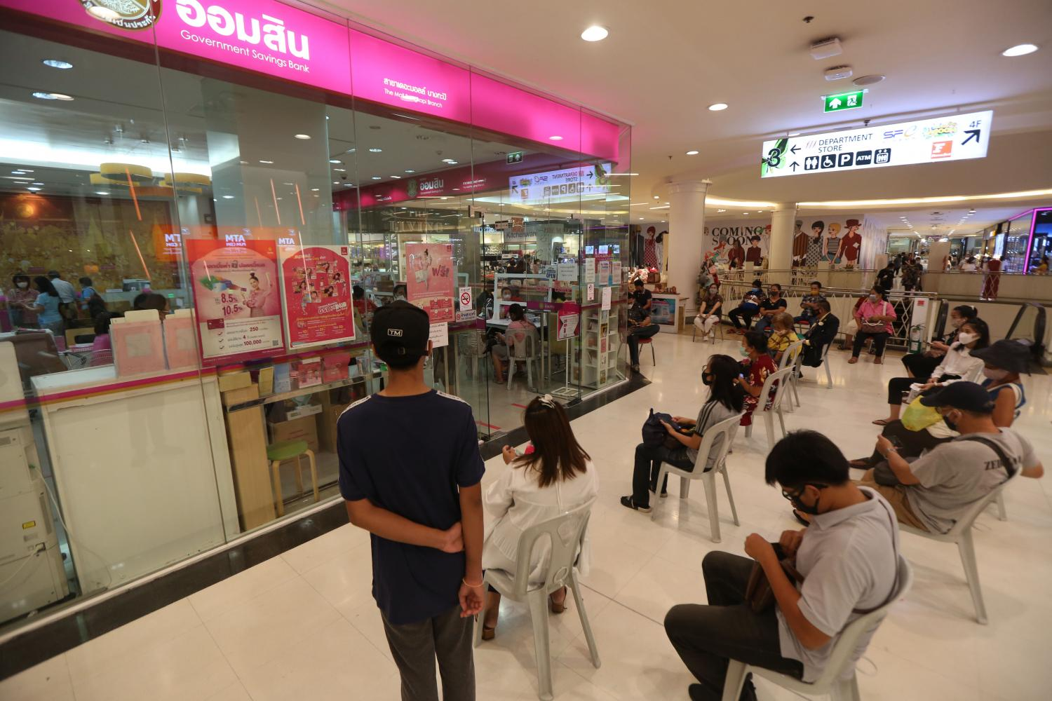Customers maintain social distance while waiting in the queue at a GSB branch.(Photo by Varuth Hirunyatheb)