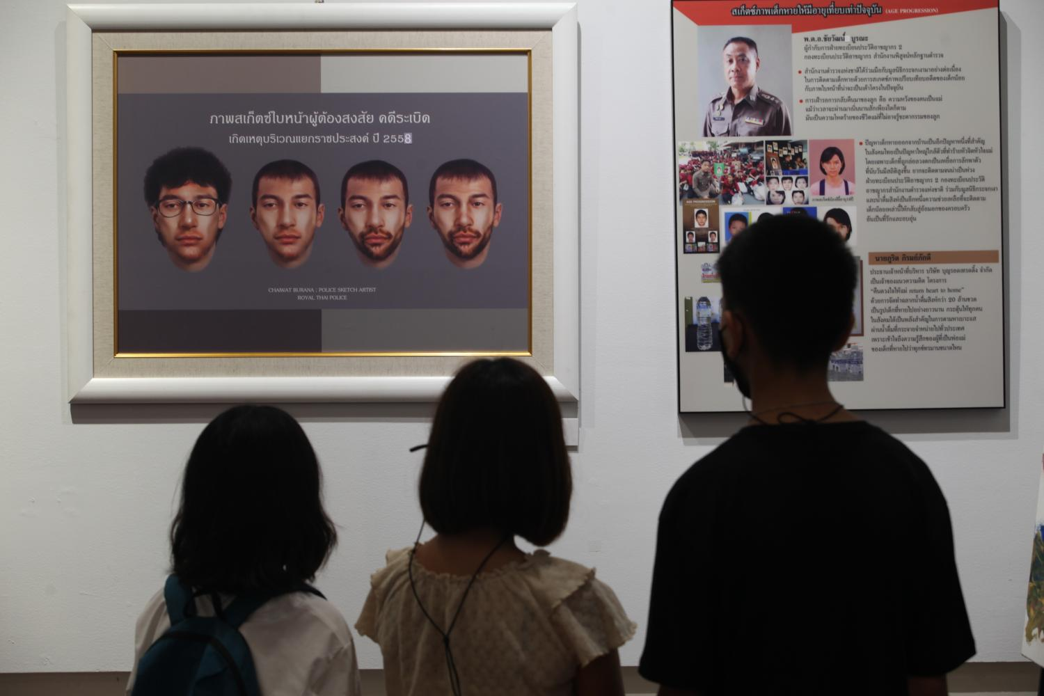 Young visitors look at digitally-sketched faces of Bilal Mohammed, one of two suspects in the deadly explosion at the Erawan Shrine at Ratchaprasong intersection in 2014, at an exhibition featuring faces of missing people at Silpa Bhirasri's House in Bangkok. (Photo by Jetjaras Na Ranong)