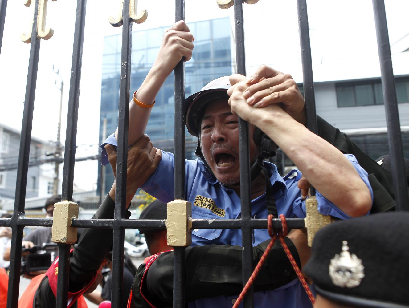A man tries to climb up a fence at the Finance Ministry out of frustration after he missed out on the government's 5,000-baht handout despite being eligible. Nutthawat Wicheanbut