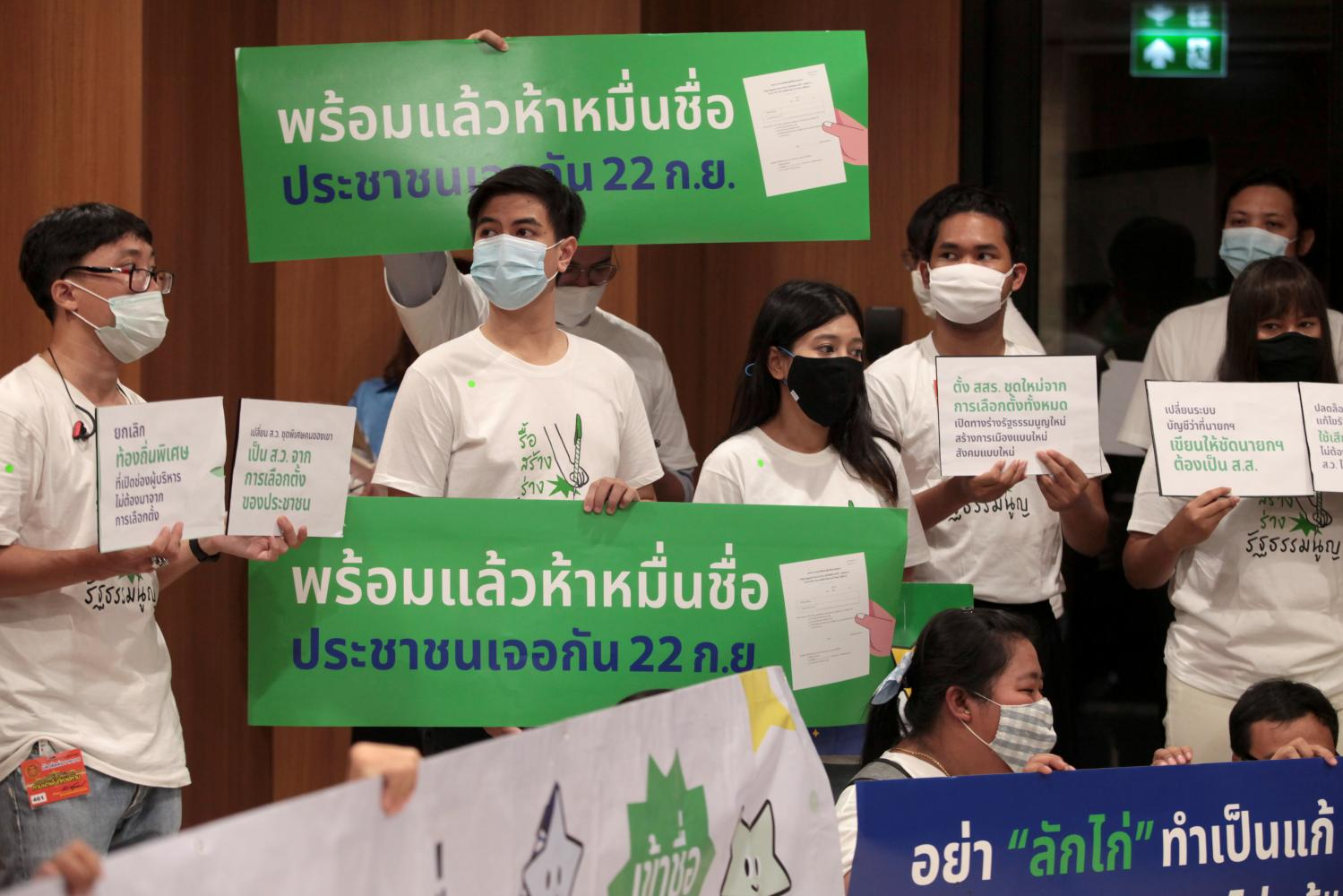 Activists hold up placards at a gathering to submit a petition signed by more than 70,000 people backing their version of a draft constitutional amendment at parliament yesterday. Chanat Katanyu