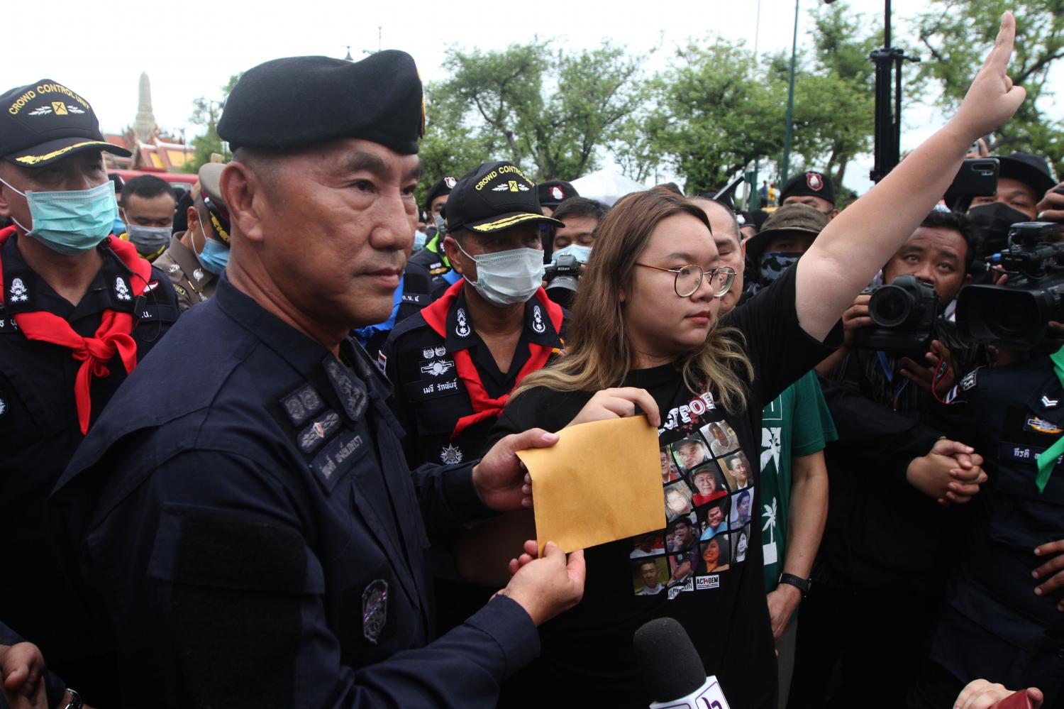 Student leader Panusaya Sithijirawattanakul hands over an envelope containing demands for reform of the monarchy to Metropolitan Police Bureau chief Pol Lt Gen Phukphong Phongpetra after police blocked them from marching to the Office of the Privy Council on Sunday.(Photo by Wichan Charoenkiatpakul)