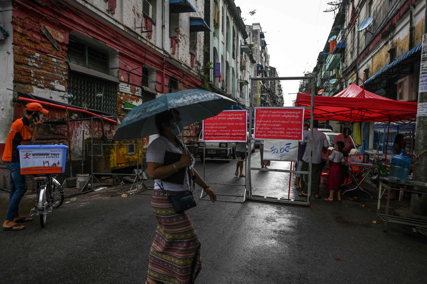 A woman walks past a barrier blocking access to minor roads in Yangon. Much of Myanmar is under lockdown because of a surge in Covid-19. (AFP photo)
