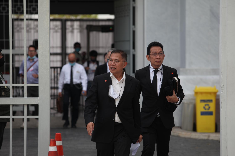 Watana Muangsook, left, leaves the Supreme Court after posting a 10-million-baht bail.(Photo by Apichart Jinakul)