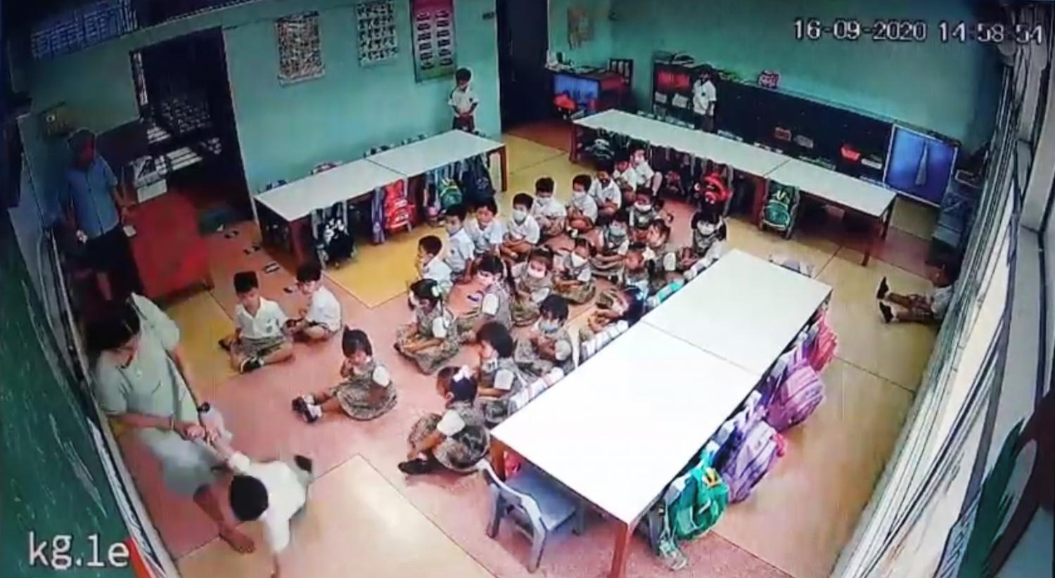 How not to teach: An image from a video showing a teacher throwing a three-year-old student to the floor in the presence of other staff members at the privately-run Sarasas Witaed Ratchaphruek School in Pak Kret district of Nonthaburi on Wednesday.