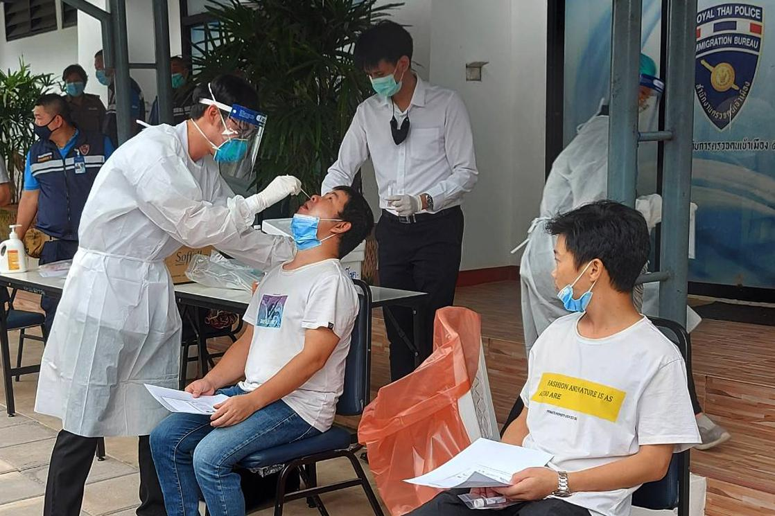 A health official in Chiang Mai conducts swab testing for a group of 19 Chinese nationals arrested for illegal entry. The suspects, who tested negative for Covid-19, are being detained at an immigration centre and will be tested again during Oct 11-13.(Photo by Panumet Tanraksa)