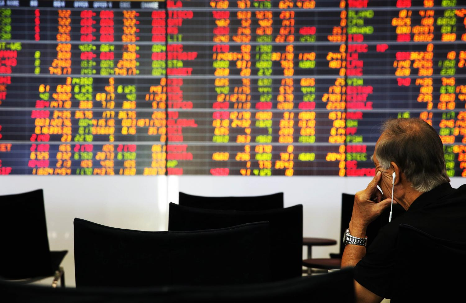 An investor looks at electronic display of stock indices at the Stock Exchange of Thailand. Wisit Thamngern