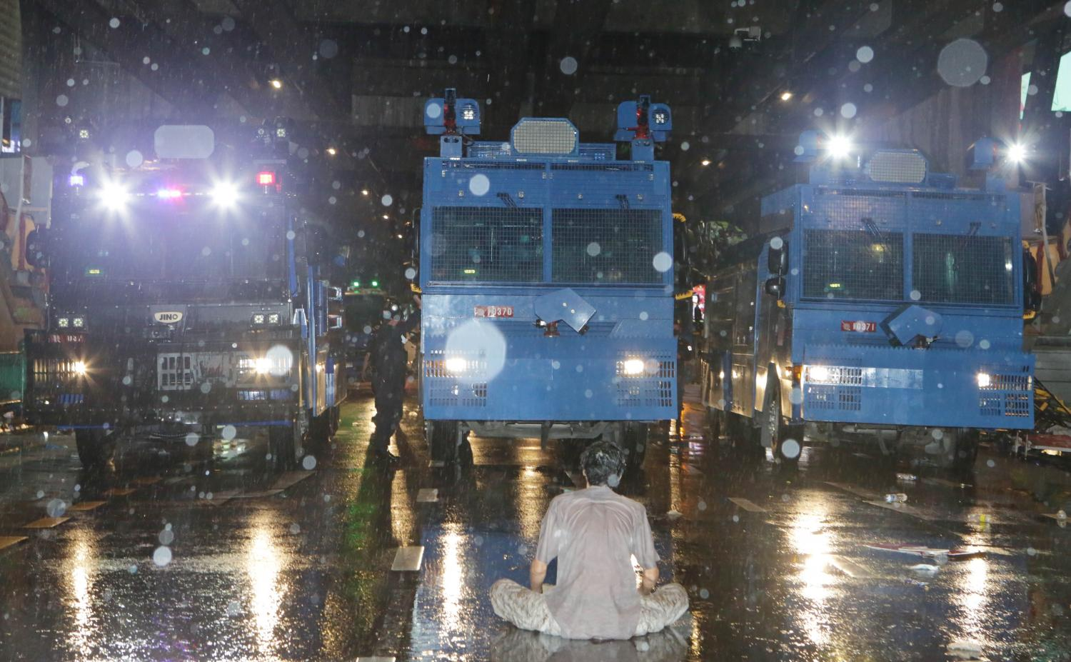 A lone protester sits in front of police water cannon trucks to prevent them from advancing on demonstrators who gathered peacefully at Pathumwan intersection on Friday.Apichit Jinakul
