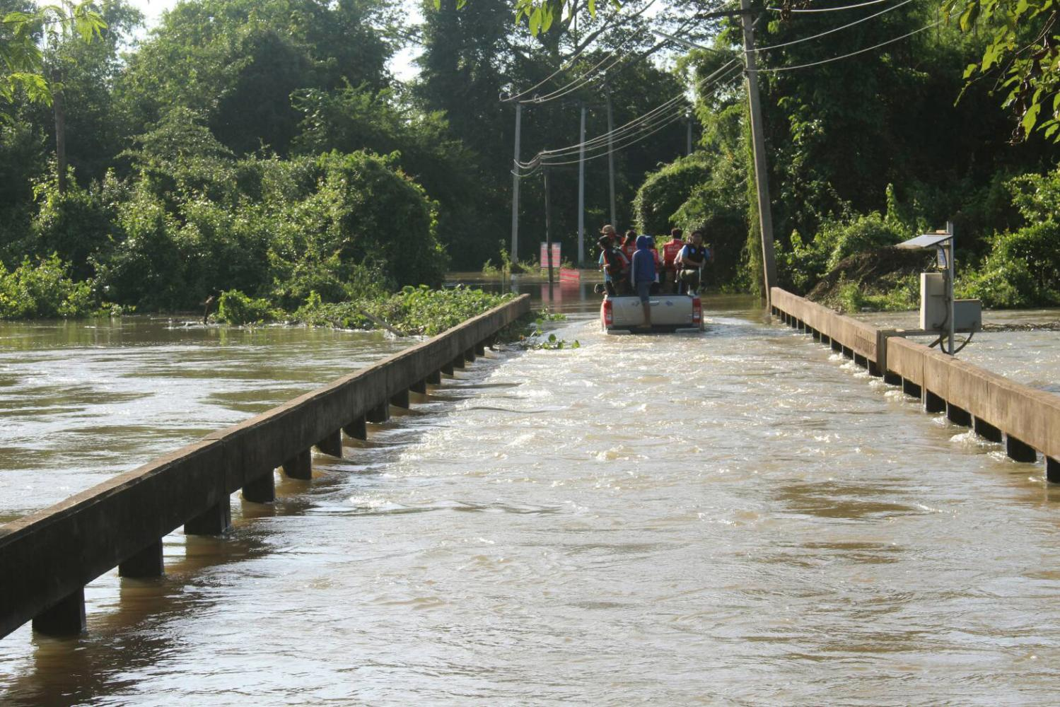 A pickup truck carrying residents drives slowly over a flooded bridge in Ban Rai village in Chok Chai district of Nakhon Ratchasima. PRASIT TANGPRASERT