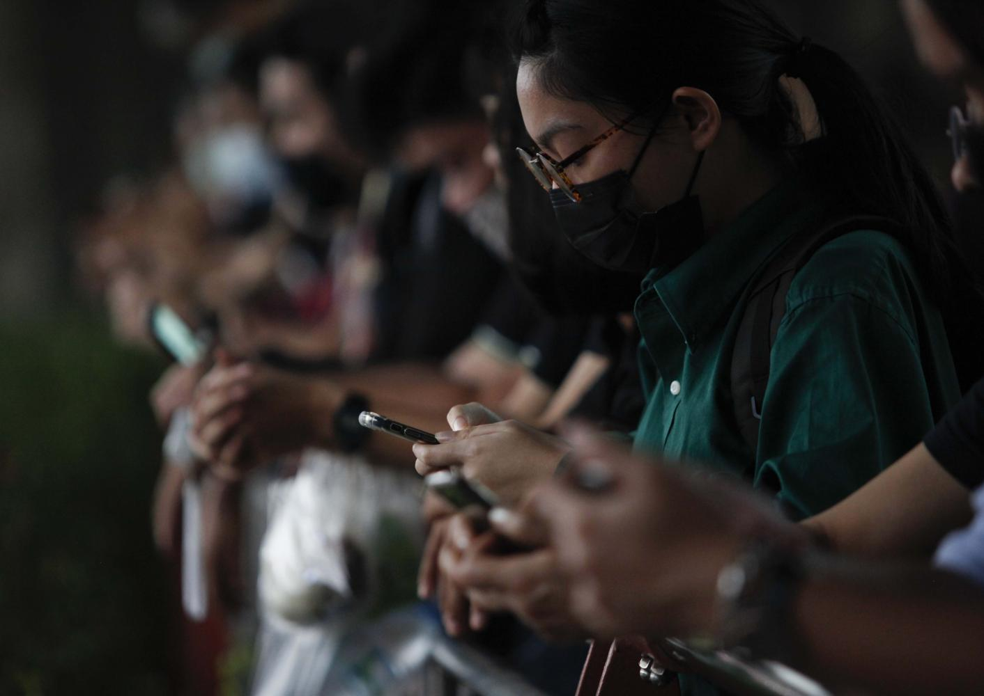 Young protesters check messages on their mobile phones in this file photo taken on Oct 20. Pattarapong Chatpattarasill
