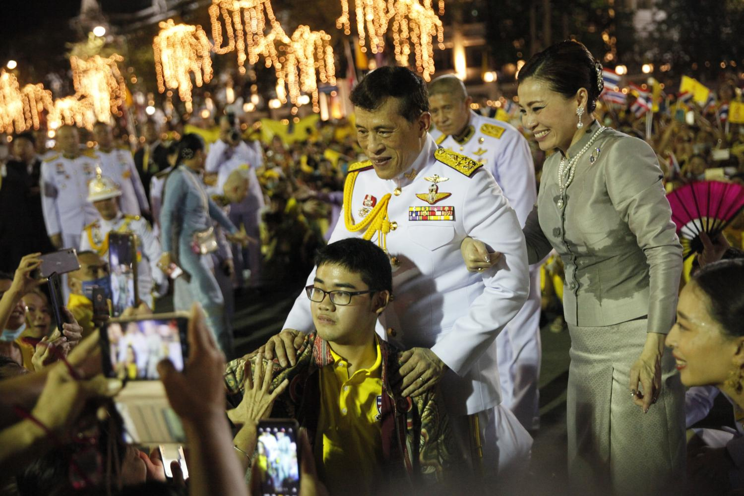 Their Majesties the King and the Queen allow a Mathayom 4 student from Wat Ratchabophit School to take a selfie with them while they greeted a royalist crowd outside the Grand Palace on Sunday night. (Photo by Wichan Charoenkiatpakul)