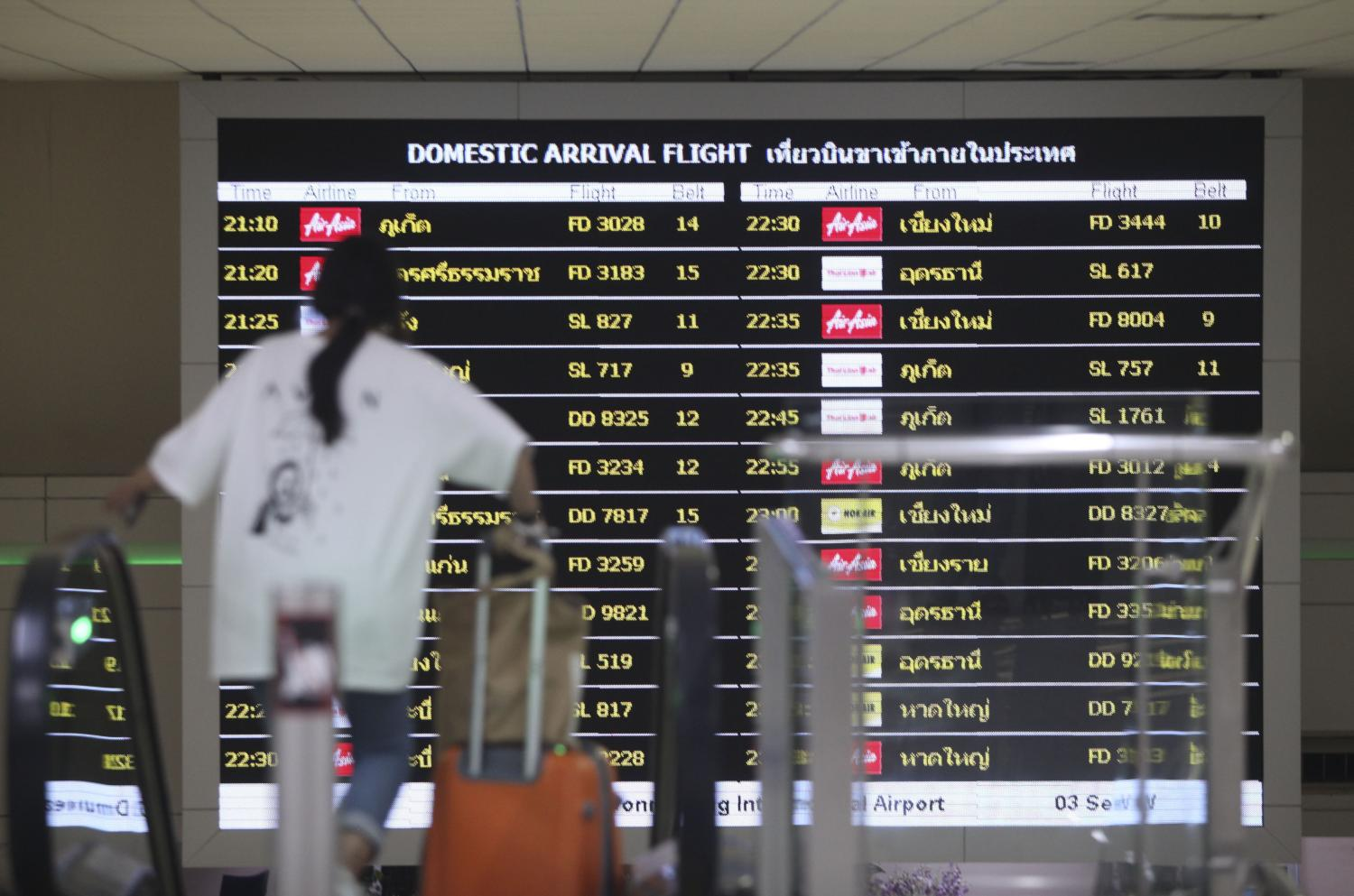 A passenger walks past a flight schedule display at Don Mueang airport. The Thai Travel Agents Association expects tourism will improve by June at a gradual pace.