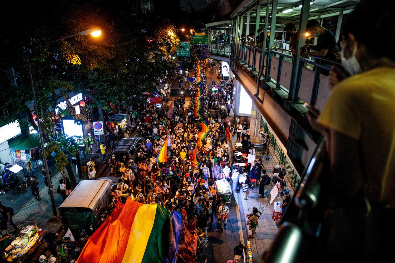 LGBTQ activists carry a giant rainbow banner during the Pride Parade as they march towards Silom on Saturday night.