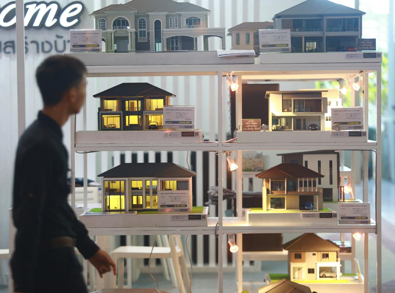 A man browses townhouse models displayed at a House and Condo Fair.