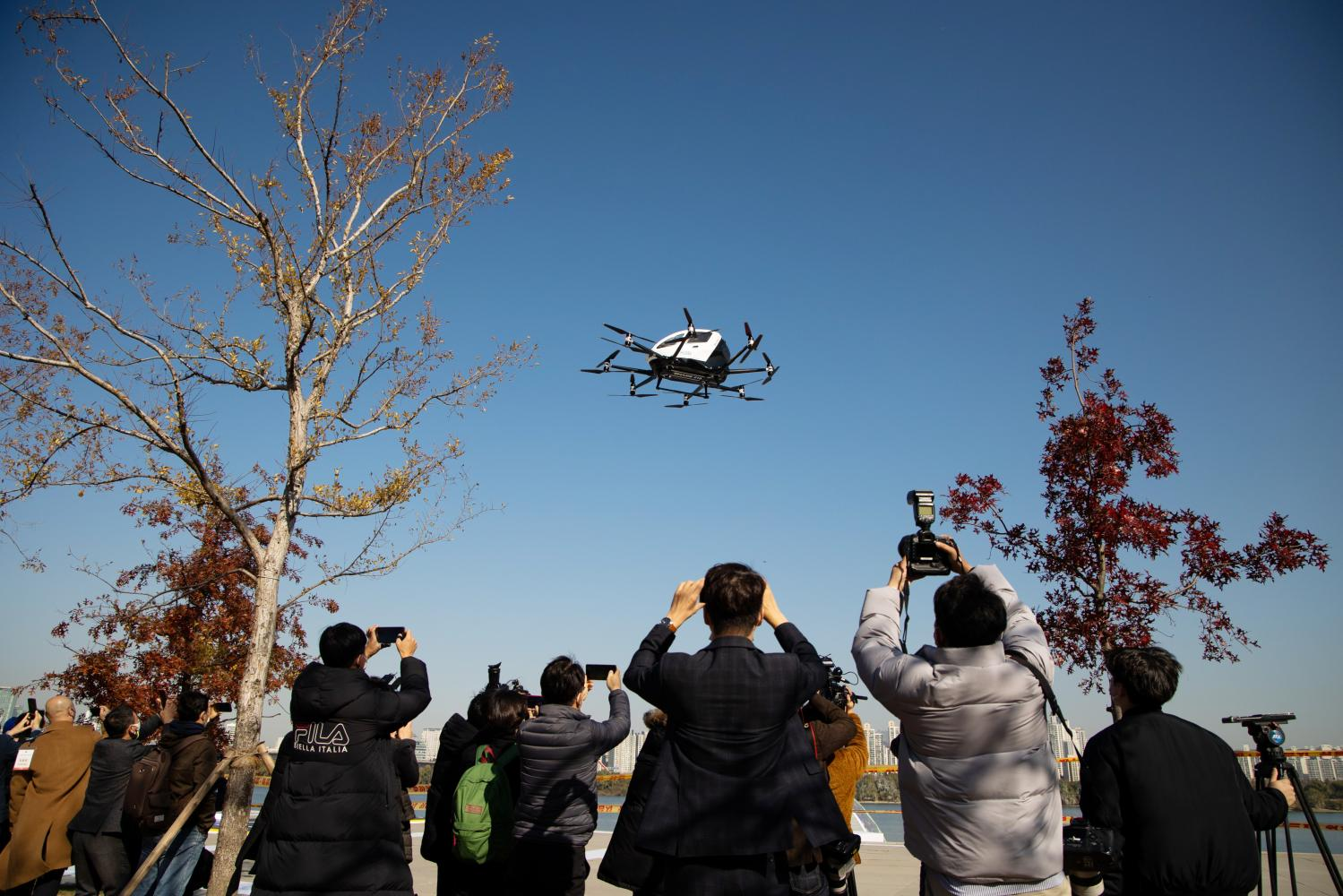 Members of media take photographs and film the EHang 216 during a demonstration in Seoul on Wednesday. (Bloomberg photo)